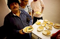 An undocumented Central American migrant traveling across Mexico to work in the United States make a line for food at a shelter located along the rail...