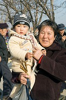 Chinese woman holding infant in rural farm village of Hui Wen in Shandong province, China  Skewered meat kebab snack in hand