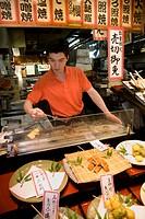 Japan, Honshu island, Kyoto, man cooking tempura at food stall at Nishiki Ichiba Market