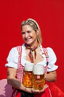 Germany, Munich. Waitress with beer steins poses at Oktoberfest celebration. Credit: Dennis Flaherty / Jaynes Gallery / DanitaDelimont.com