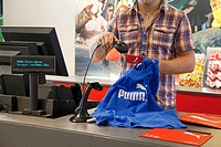 Factory outlet store of the sports goods manufacturer PUMA AG, goods being scanned and packed at the checkout, Herzogenaurach, Bavaria, Germany, Europ...