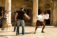 Croatia, Dalmatia, Dubrovnik. Men fencing while being filmed outside of Rector´s Palace. The historic center of Dubrovnik is a UNESCO World Heritage s...