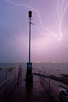 Thunderstorm with lightning and a storm warning light, man watching the thunderstorm while standing, Lake Constance, Konstanz, Baden-Wuerttemberg, Ger...