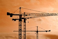 Tower crane silhouettes at a construction site