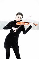 Woman, 19 years, with violin in a snowy winter landscape