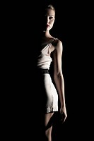Young woman in a white dress in light and shadow, fashion