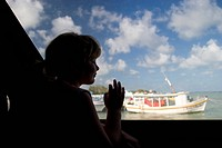 Mexico, Yucatan, Isla Mujeres Island of Women, girl age 5 looking through ferry boat window MR