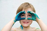 Little boy, three years, looking through his hands painted with finger paint