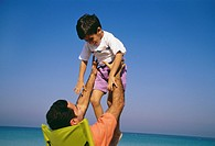 A father hoisting his son near the vast sea.