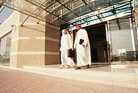 Two Arabs converse regarding their business while leaving from the commercial building.