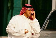 An Arab converses on the mobile phone near the car.