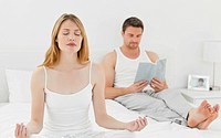 Woman practicing yoga while her husband is reading on the bed