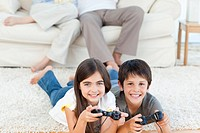 Children playing videogames while parents are talking at home