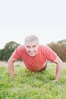 Smiling man doing push_ups in field