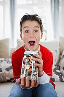 Surprised boy holding jar full of coins (thumbnail)