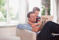 Father and son reading newspaper together (thumbnail)