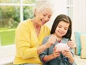 Grandmother putting coin into granddaughter's piggy bank (thumbnail)