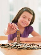 Smiling girl stacking coins
