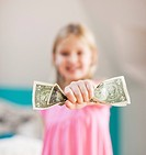 Girl holding one dollar bills