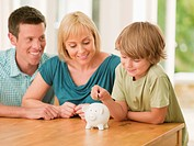 Parents watching son putting coin into piggy bank