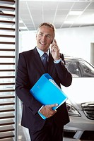 Salesman holding binder and talking on cell phone in automobile showroom