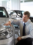 Salesman cleaning new car in showroom