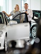 Woman and salesman looking at new car in showroom