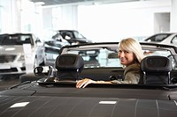 Woman sitting in convertible in automobile showroom