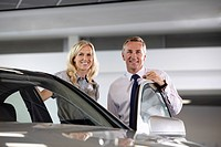 Sales people standing with new car in showroom