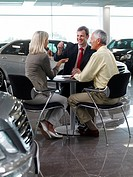 Salesman handing car key to couple in automobile showroom