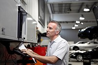 Mechanic using computer in auto repair shop