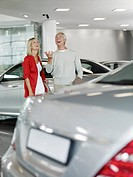 Couple tossing car key in automobile showroom