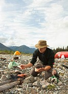 Man cooking on a camp fire, BBQ, grilling hamburger, gravel bar, tent behind, camping, Wind River, Yukon Territory, Canada
