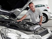 Mechanic working on engine in automobile showroom