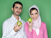 Couple holding green apple
