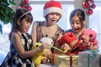 Three girls, 10 and 12 years, unwrapping Christmas presents