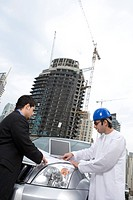 Businessmen conversing at construction site