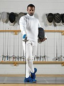 Portrait of a fencer wearing fencing uniform in a gym