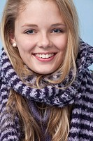 Young woman with knitted sweater and striped scarf