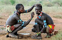 Men from the Hamar tribe painting each other for the initiation ritual leap over the cattle, southern Omo valley, Ethiopia, Africa