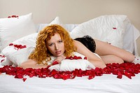 Woman on bed with rose petals.
