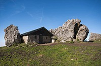 Stone house on Steinlingalm alp, built next to large limestone rocks, Kampenwand mountain massif, Chiemgau, Kampenwand mountain, Upper Bavaria, German...