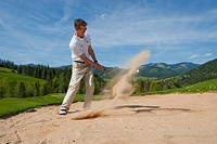 Golf player standing in the bunker batting the golf ball out of the sand, on alpine golf course, Achenkirch, Tyrol, Austria, Europe