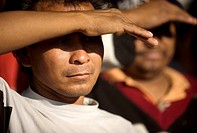 Central American migrants traveling across Mexico to work in the United States cover their eyes with his hand at the Catholic priest Alejandro Solalin...