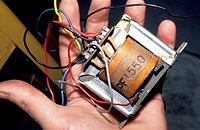hand holding old fashioned transformer with wires protruding