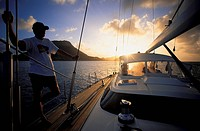 Man on sailing boat at sunset, Iles des Saintes, Guadeloupe, Caribbean, America