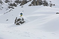 Skier jumping over rock, Arosa, Canton of Grisons, Switzerland