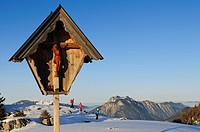 Wayside cross and people snowshoeing, Eggenalm, Reit im Winkl, Chiemgau, Upper Bavaria, Bavaria, Germany, Europe