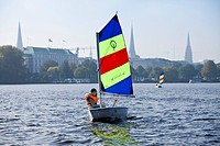 Girl in sailing dinghy Optimist on outer Alster, Hamburg, Germany