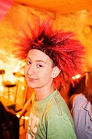 Portrait of teenage boy wearing red spiky wig